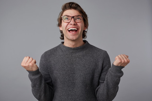 Foto van jonge blije man met bril draagt in grijze trui, staat over grijze achtergrond. breed lacht en balde vuisten, won de miljoen en voelt geluk.