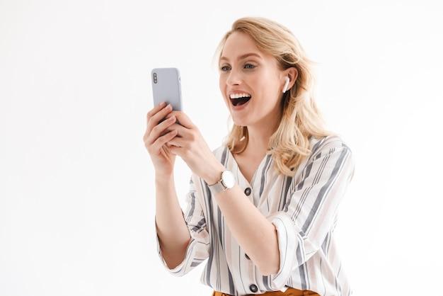 Foto van jonge blije vrouw die polshorloge draagt die cellphone en earpod gebruikt die over witte muur wordt geïsoleerd