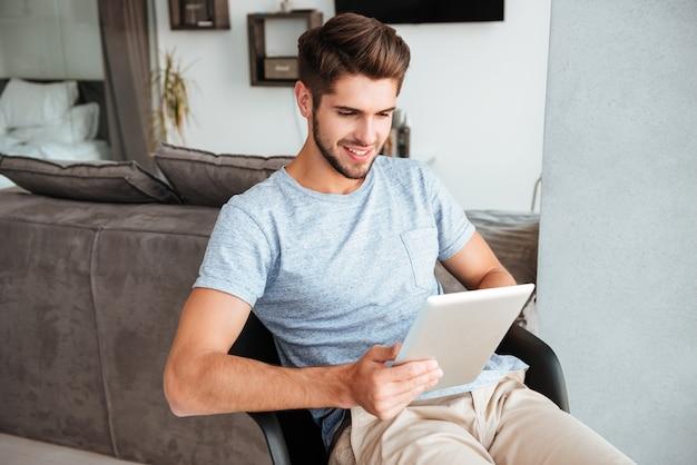 Foto van jonge bruids man gekleed in grijs t-shirt zittend op een stoel en tablet te houden