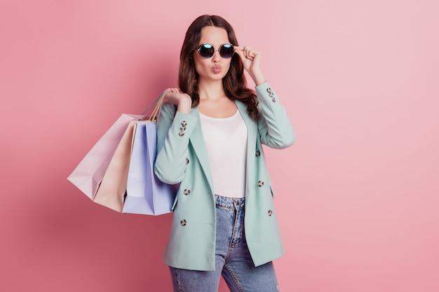 Foto van jonge brunette vrouw met boodschappentassen stuurt luchtkus die zich voordeed op roze muur