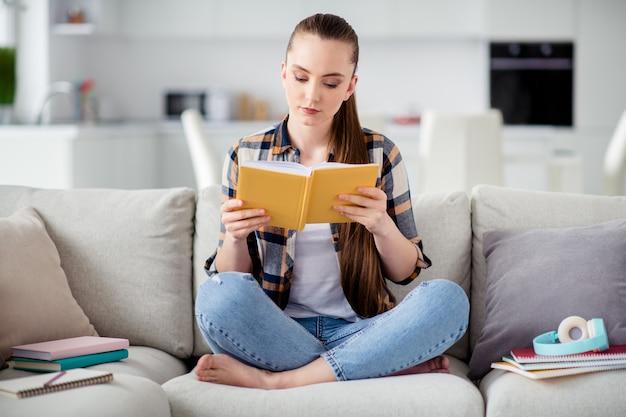 Foto van jonge dame student houdt boek dagboek handen zitten sofa benen gekruist dromerig