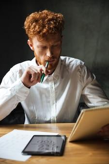 Foto van jonge denken readhead bebaarde man in wit overhemd, het lezen van notities, zittend aan houten tafel