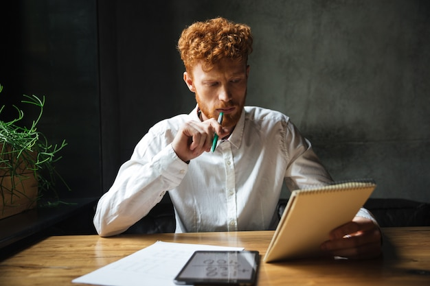 Foto van jonge denken readhead bebaarde man, met notitieboekje en groene pan, zittend aan houten tafel