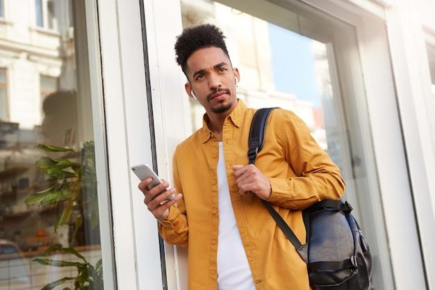 Foto van jonge denkende afro-amerikaanse man in geel overhemd, lopend over straat, houdt telefoon vast, luistert naar nieuwe podcast, kijkt twijfel.