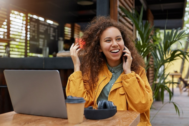 Foto van jonge donkere gekrulde vrouw die op een caféterras zit, gekleed in een gele jas, werkt op een laptop, lacht en praat aan de telefoon met een vriend, koffie drinkt.