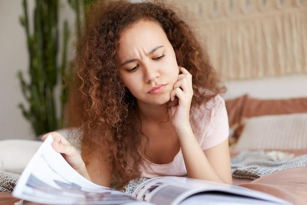 Foto van jonge fronsende afro-amerikaanse afro-amerikaanse dame met krullend haar, ligt op het bed en raakt de kin, peinzend het nieuwe nummer van het favoriete tijdschrift te lezen.