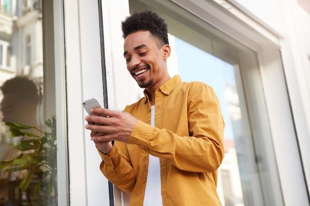 Foto van jonge gelukkig donkere man in geel shirt op straat lopen, telefoon houdt, chatten met vriendin, in grote lijnen glimlachen, ziet er vrolijk uit.