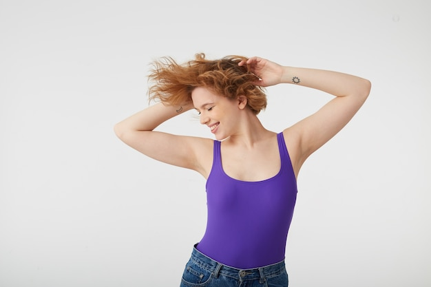 Foto van jonge gelukkig schattig korthaar meisje draagt in paars shirt dansen met opgeheven armen, haren vliegen uit elkaar in verschillende richtingen, genieten van muziek en leven.