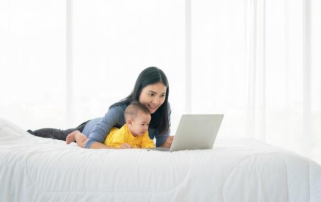 Foto van jonge gelukkige thaise moeder met haar baby die laptop op bed met behulp van. thuiscomfort. zorg en aandacht. werk vanuit huis.