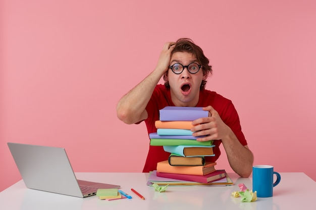 Foto van jonge geschokt man in glazen zit bij de tafel en werkt met laptop en boeken, leunde op een stapel boeken, kijkt verbaasd met wijd open mond. geïsoleerd op roze achtergrond.