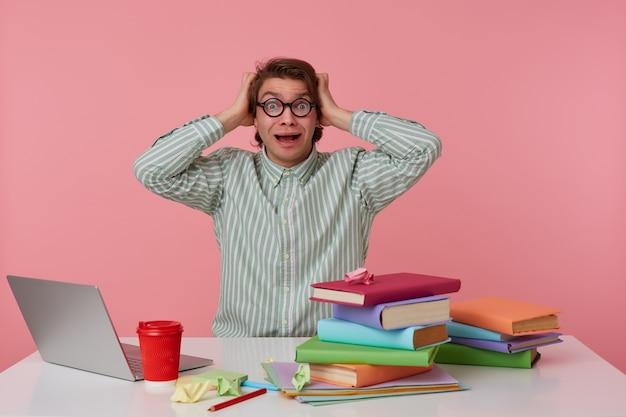 Foto van jonge geschokte man in glazen, zit bij de tafel en werkt met laptop, houdt zijn hoofd vast en kijkt verbaasd en bang, geïsoleerd op roze achtergrond.