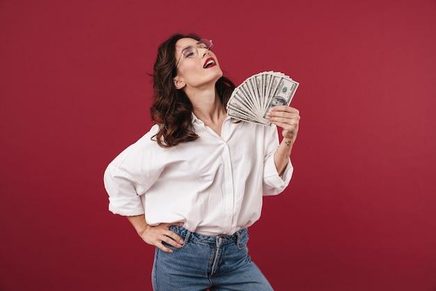 Foto van jonge geweldige mooie vrouw geïsoleerd op rode muur aanhouden van geld.