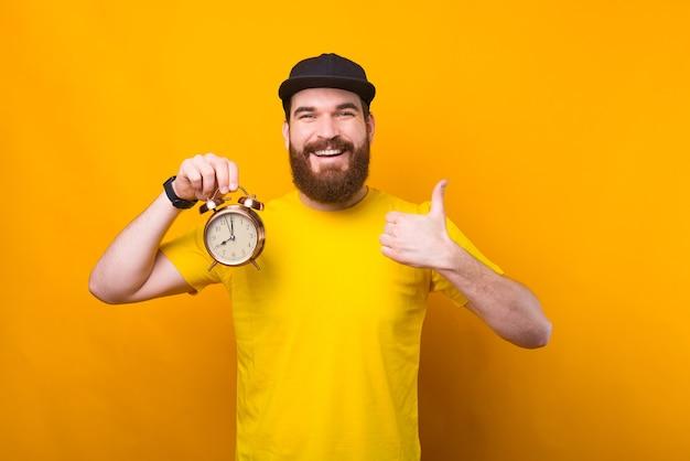 Foto van jonge hipster man met wekker en duim opdagen, tijd plannen