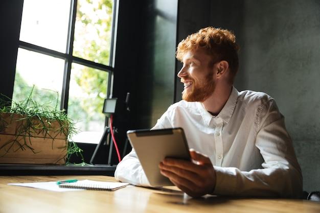 Foto van jonge knappe readhead bebaarde man met tablet, kijken naar groot raam