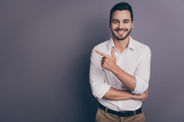 Foto van jonge knappe zaken man vriendelijk glimlachen wijzende vinger op lege ruimte