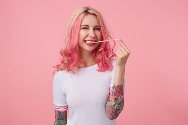 Foto van jonge lachende mooie roze harige dame met getatoeëerde handen, draagt in wit t-shirt, geniet van aardbei kauwgom, looks stands.