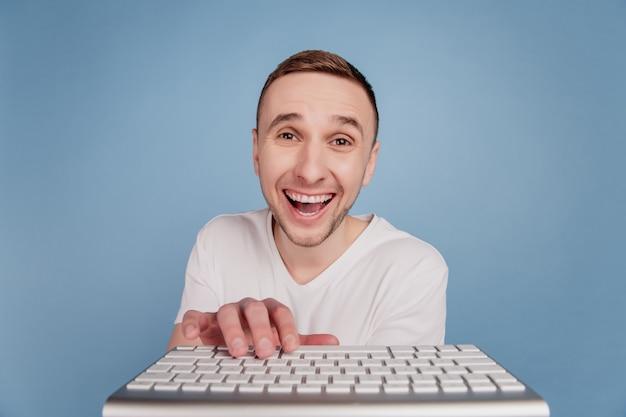 Foto van jonge man gelukkig positieve glimlach lachen in wit t-shirt typen op computertoetsenbord geïsoleerd over blauwe kleur achtergrond