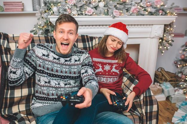 Foto van jonge man heeft spel gewonnen. de vrouw is het kwijt. ze is boos terwijl de man gelukkig is. hij juicht en schreeuwt.