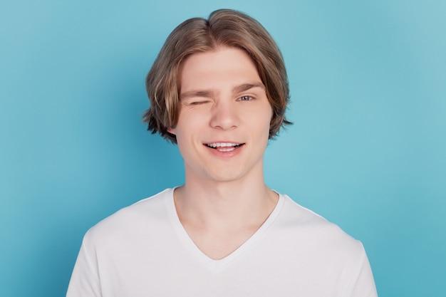 Foto van jonge man knipoogt oog slijtage wit t-shirt geïsoleerd op blauwe achtergrond