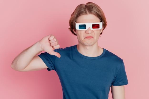 Foto van jonge man met 3d-bril, kijk naar film, duim omlaag, niet leuk, geïsoleerd over pastelkleurige achtergrond