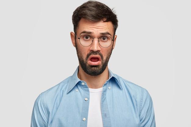 Foto van jonge man met donkere stoppels maakt verveeld gezicht, luistert naar iets met gebrek aan interesse, heeft een ontevreden uitdrukking, gekleed in een blauw shirt, opent zijn mond van ongenoegen, geïsoleerd over witte muur