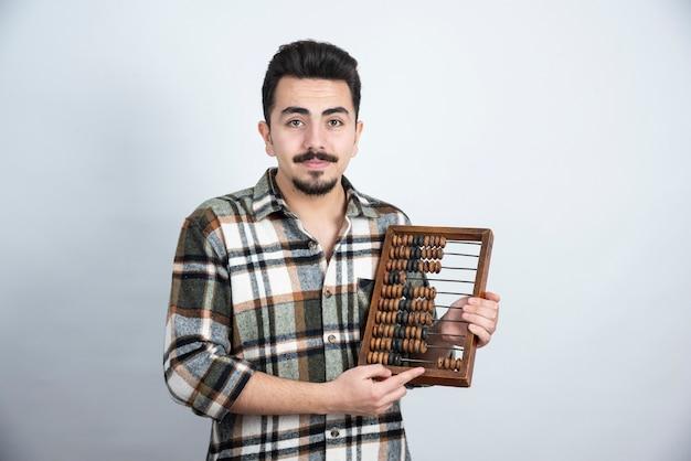 Foto van jonge man met houten tellende kralen die zich over witte muur bevinden.