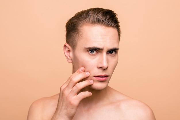 Foto van jonge man poseren geïsoleerd op pastel beige