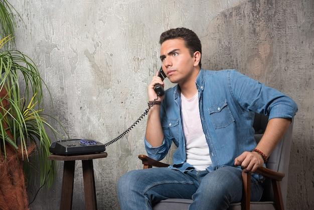 Foto van jonge man praten over de telefoon en zittend op een stoel. hoge kwaliteit foto