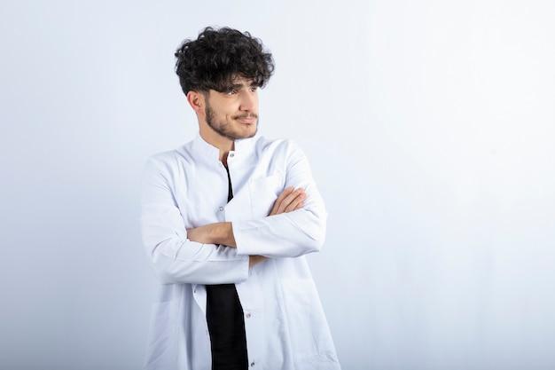 Foto van jonge mannelijke arts die zich op grijs bevindt.
