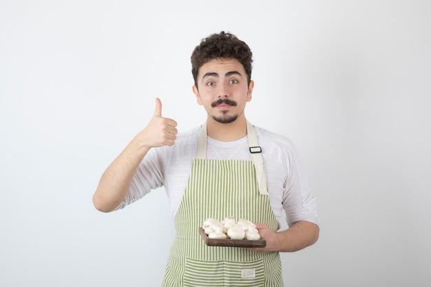 Foto van jonge mannelijke kok die rauwe champignons op wit houdt