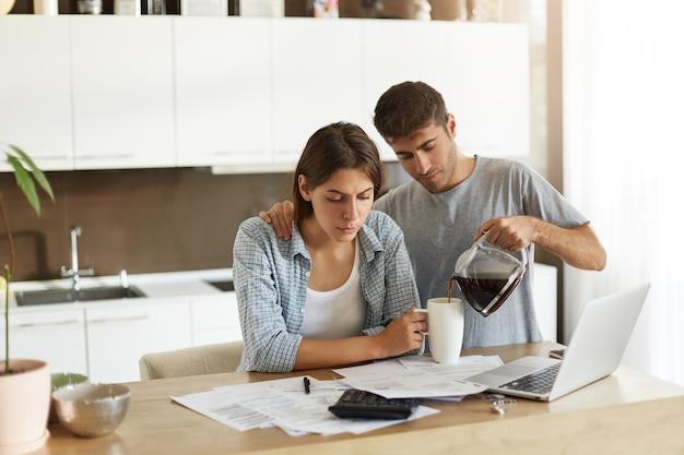 Foto van jonge mannen en vrouwen die samen thuis papierwerk doen: serieuze vrouw aan eettafel zitten met papieren en laptopcomputer, rekeningen berekenen terwijl haar man koffie aan haar serveert