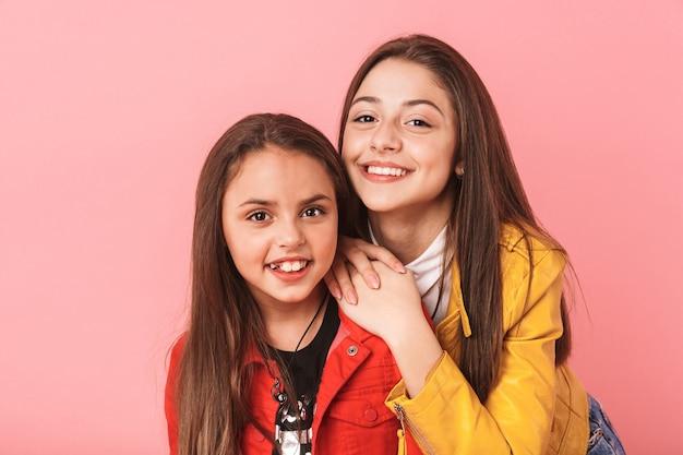 Foto van jonge meisjes in casual knuffelen samen, geïsoleerd over rode muur