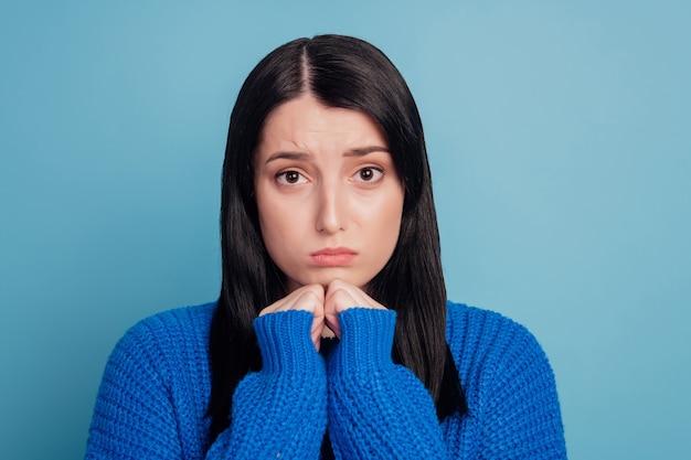 Foto van jonge meisjeshanden raken kin ongelukkig verdrietig overstuur beledigd gestrest depressief mislukken geïsoleerd over blauwe kleur achtergrond