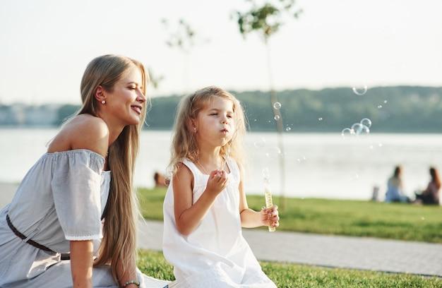 Foto van jonge moeder en haar dochter die goede tijd hebben op het groene gras met meer bij achtergrond.