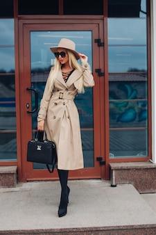 Foto van jonge mooie blanke vrouw met blond haar in zwarte jurk, witte jas, zwarte schoenen met witte hoed, zwarte zonnebril en zwarte tas