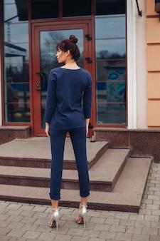 Foto van jonge mooie blanke vrouw met donker haar in donkerblauwe blouse en donkerblauwe broek, witte schoenen met witte tas staat terug naar de camera