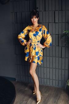 Foto van jonge mooie blanke vrouw met donker haar in gele en blauwe jurk, gouden schoenen toont verschillende poses voor de camera