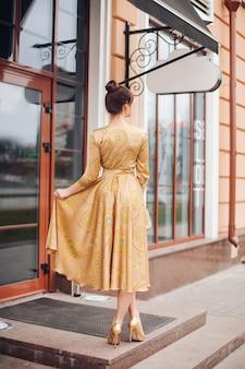 Foto van jonge mooie blanke vrouw met donker haar in gouden jurk en gouden schoenen toont verschillende stands in de buurt van het prachtige gebouw