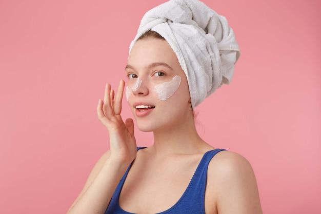 Foto van jonge mooie blije dame met natuurlijke schoonheid met een handdoek op haar hoofd na het douchen, staat en zet op gezichtscrème, kijkt weg.