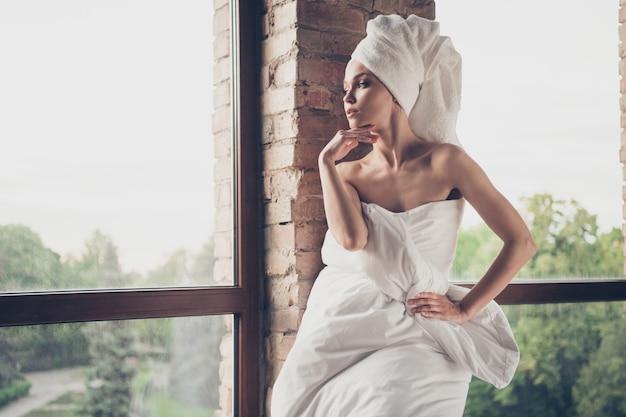 Foto van jonge mooie dame ontspannen spa huis procedures quarantaine thuis blijven naakte schoonheid schouders kijken groot raam minded draag alleen deken hoofd tulband woonkamer binnenshuis