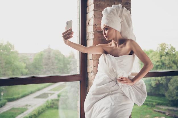 Foto van jonge mooie dame ontspannen spa huis procedures quarantaine thuis blijven naakte schouders vasthouden telefoon maken selfies blogger alleen dragen deken hoofd tulband groot raam woonkamer binnenshuis