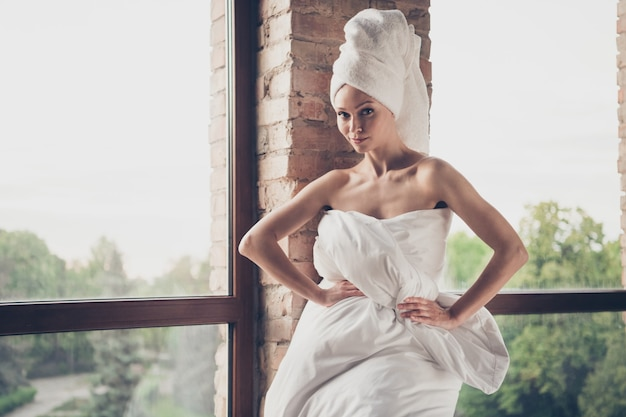 Foto van jonge mooie flirterige dame spa huis procedures quarantaine thuis blijven naakte schoonheid schouders poseren draag alleen deken hoofd tulband woonkamer groot raam binnenshuis