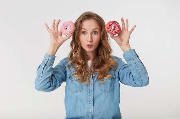 Foto van jonge mooie man, houdt donuts aan het hoofd en lippen buigen, geïsoleerd op witte achtergrond.