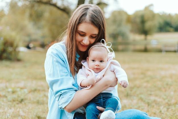 Foto van jonge mooie moeder buiten zitten met haar kleine babymeisje