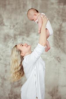 Foto van jonge mooie moeder met schattige babyjongen, glimlachend mama lift haar schattige zoon, mooie vrouw vrolijk kindje overgeven op grijze achtergrond, gezonde en gelukkige familie, liefde concept