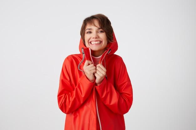 Foto van jonge mooie vrolijke kortharige dame in rode regenjas, breed glimlachend, geniet van het leven, voelt geluk. staand.