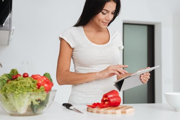 Foto van jonge mooie vrouw leest recept van tabletcomputer in de keuken. tabletcomputer kijken.