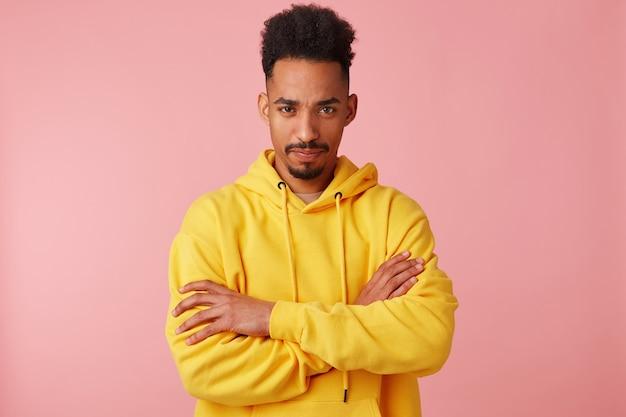 Foto van jonge ontevreden afro-amerikaanse man in gele hoodie, beledigd kijken, staande met gekruiste armen.