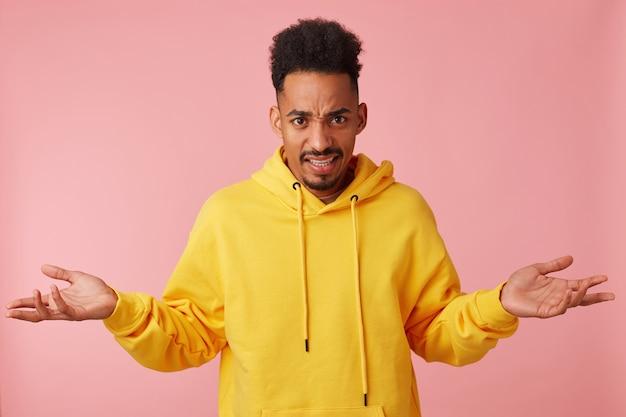 Foto van jonge ontevreden afro-amerikaanse man in gele hoodie, fronsend en werpt zijn handen in een misverstand over wat er gebeurt, op zoek.