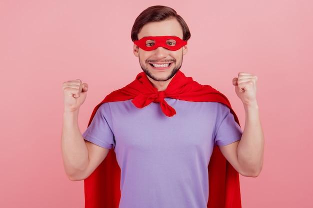 Foto van jonge opgewonden superman, blije positieve glimlach, verheug je over overwinningssucces geïsoleerd over roze kleurachtergrond